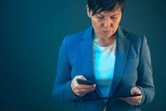 Onderneemster die mobiele telefoon en tabletcomputer met behulp van royalty-vrije stock afbeeldingen