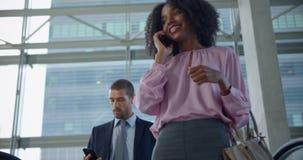 Onderneemster die mobiele telefoon op roltrap in een modern bureau 4k met behulp van stock video