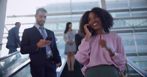 Onderneemster die mobiele telefoon op roltrap in een modern bureau 4k met behulp van stock footage