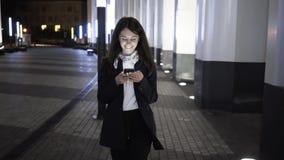 Onderneemster die in nachtstad lopen die haar smartphone nemen en godstekst krijgen stock video