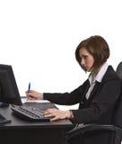 Onderneemster die nota's neemt bij haar bureau. Stock Fotografie
