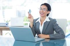 Onderneemster die online het winkelen in bureau doet Stock Afbeelding