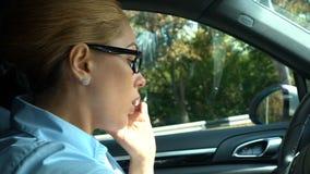 Onderneemster die op cellphone spreken, die op bestuurderszetel zitten in auto, veiligheidsregels stock video