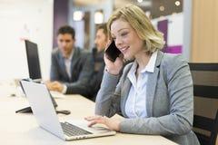Onderneemster die op de mobiele telefoon in modern bureau spreken Stock Afbeeldingen