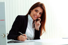 Onderneemster die op de telefoon en het schrijven nota's spreekt Stock Fotografie