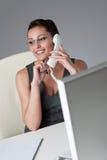Onderneemster die op de telefoon op kantoor spreekt stock fotografie