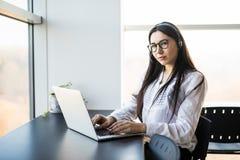 Onderneemster die op de telefoon spreken terwijl het werken aan haar computer Royalty-vrije Stock Foto's