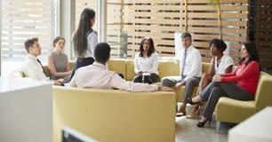 Onderneemster die op een teamvergadering voorstellen op zitkamergebied royalty-vrije stock fotografie