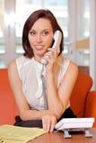 Onderneemster die op landline telefoon converseert stock fotografie
