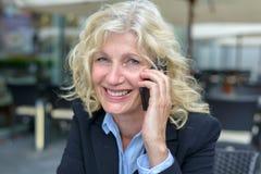 Onderneemster die op middelbare leeftijd op mobiel spreken stock afbeeldingen