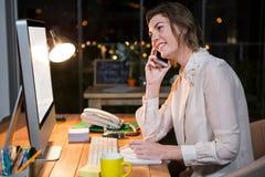 Onderneemster die op mobiele telefoon spreken terwijl het werken aan computer bij haar bureau Stock Afbeelding