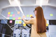 Onderneemster die op multi gekleurde kleverige nota's over glas schrijven Stock Foto