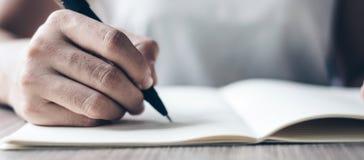 Onderneemster die op notitieboekje in bureau, hand schrijven van de pen van de vrouwenholding met handtekening op document rappor royalty-vrije stock afbeeldingen