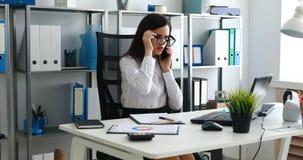 Onderneemster die op smartphone spreken en in modern bureau werken stock video