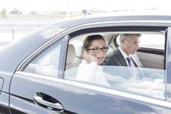 Onderneemster die op smartphone spreken terwijl het zitten met collega in auto stock foto's