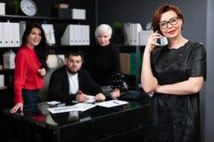 Onderneemster die op telefoon op achtergrond van beambten spreken die project bespreken royalty-vrije stock foto