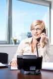Onderneemster die op telefoon spreekt Stock Foto's