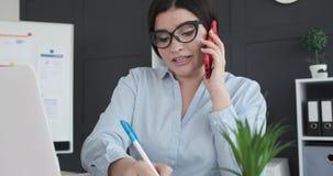 Onderneemster die op telefoon spreekt terwijl het werken op kantoor stock videobeelden