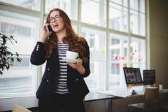 Onderneemster die op telefoon spreken terwijl het hebben van koffie in creatief bureau Royalty-vrije Stock Foto's