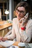 Onderneemster die op telefoon spreken terwijl het werken aan computer bij haar bureau Stock Foto
