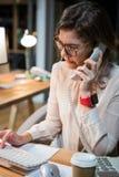 Onderneemster die op telefoon spreken terwijl het werken aan computer bij haar bureau Royalty-vrije Stock Afbeelding