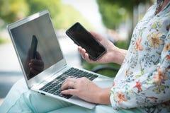 Onderneemster die in openlucht met notitieboekje en slimme telefoon werken royalty-vrije stock afbeelding
