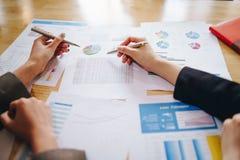 Onderneemster die pen op bedrijfsdocument richten op vergaderzaal Bespreking en analyse van gegevensgrafieken en grafieken tonen stock fotografie