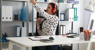 Onderneemster die in rode hoofdtelefoons video op smartphone in modern bureau schieten stock video