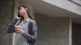 Onderneemster die slimme telefoon met behulp van terwijl het lopen met koffie stock videobeelden