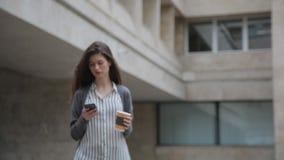 Onderneemster die slimme telefoon met behulp van terwijl het lopen met koffie stock video