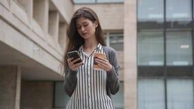 Onderneemster die slimme telefoon met behulp van terwijl status met koffie stock footage