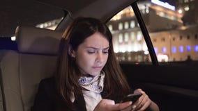 Onderneemster die terwijl het bekijken haar smartphone in een auto fronsen stock video