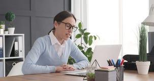 Onderneemster die videogesprek doen die laptop met behulp van op kantoor stock videobeelden