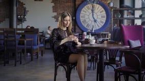 Onderneemster die in zwarte kleding middagpauze van zitting in koffie met mensen in de moderne achtergrond en gebruiken genieten stock videobeelden