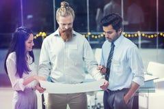 Onderneemster en zakenlieden die over blauwdruk bespreken stock fotografie