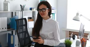Onderneemster gebruikend smartphone en glimlachend in camera in modern bureau stock videobeelden