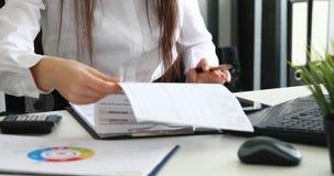 Onderneemster gebruikend smartphone en vullend documenten in modern bureau stock videobeelden