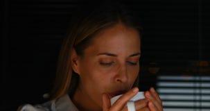 Onderneemster het drinken koffie bij nacht stock footage