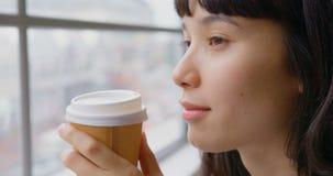 Onderneemster het drinken koffie terwijl het zitten dichtbij venster in een modern bureau 4k stock video