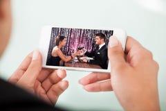 Onderneemster het letten op paar roosterende wijnglazen op cellphone Royalty-vrije Stock Fotografie