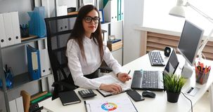 Onderneemster het vullen documenten en het werken aan laptop in modern bureau stock footage