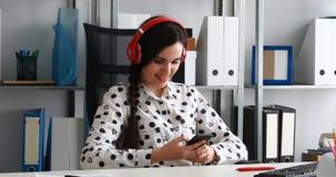 Onderneemster in hoofdtelefoons die smartphone in modern bureau gebruiken stock videobeelden