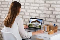 Onderneemster Looking At House op Laptop royalty-vrije stock foto's