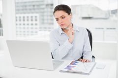 Onderneemster met grafieken en laptop in bureau Stock Foto