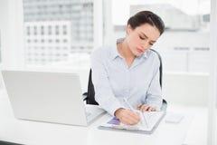Onderneemster met grafieken en laptop in bureau Royalty-vrije Stock Foto