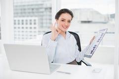 Onderneemster met grafieken en laptop die o.k. teken in bureau gesturing Royalty-vrije Stock Foto