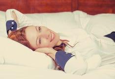 Onderneemster met handen achter hoofd die in de ruimte van het bedhotel liggen royalty-vrije stock foto