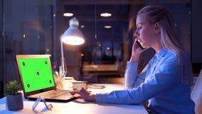 Onderneemster met het groene scherm op laptop bij nacht stock videobeelden