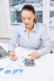 Onderneemster met laptop en grafieken in bureau Stock Foto's