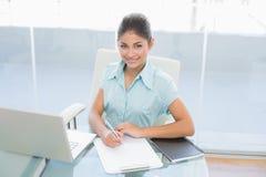 Onderneemster met laptop het schrijven document in bureau Stock Foto